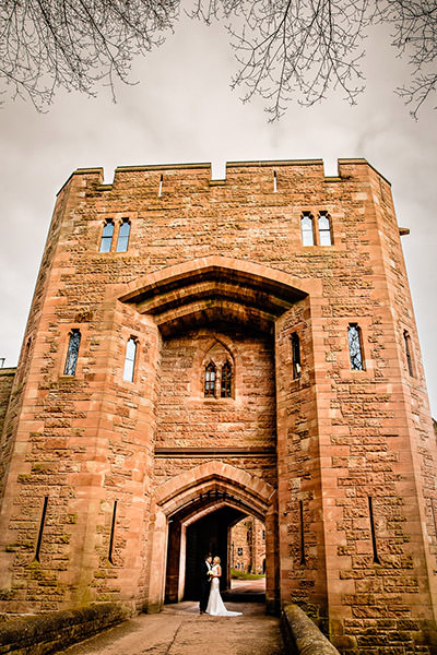 Bride and groom in front of the drawbridge at Peckforton Castle