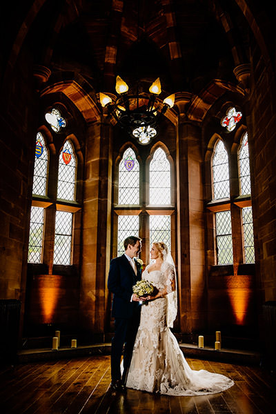 The stained glass window in the great hall with the happy couple at Peckforton Castle