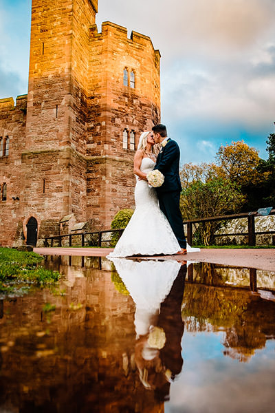 Clever reflection of the bride and groom using a puddle