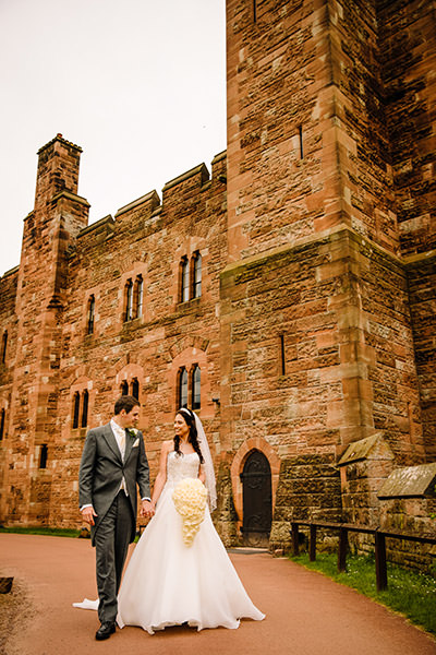 Bride and groom walking hand in hand in the grounds of peckforton castle