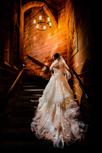 The gorgeous staircase at Peckforton castle with the back of the brides wedding dress