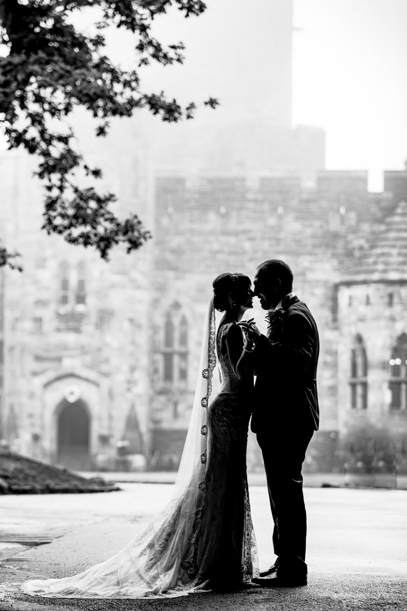 Silhouette of the bride and groom on a misty day at Peckforton Castle