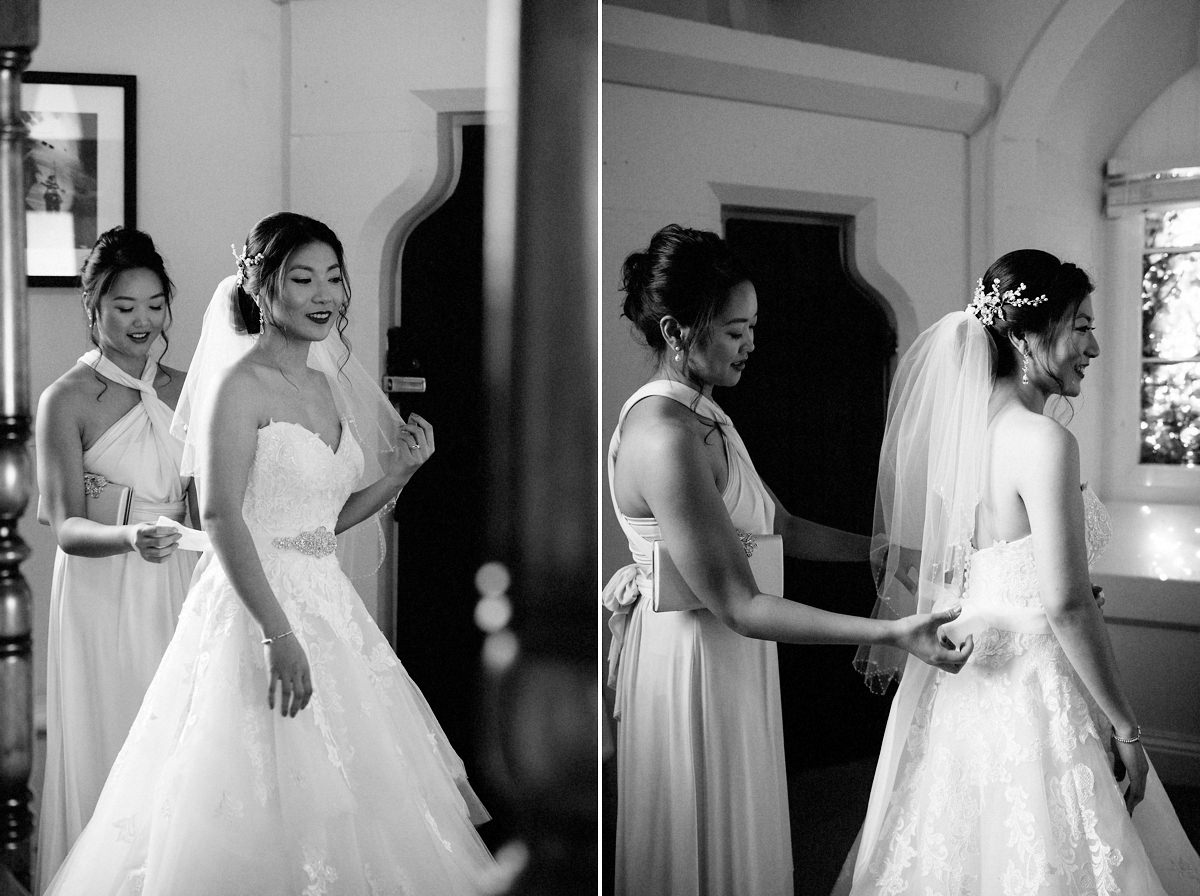 Brides sister helping her in her wedding dress