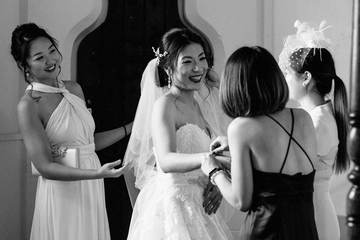 Brides mother helping bride with her wedding dress