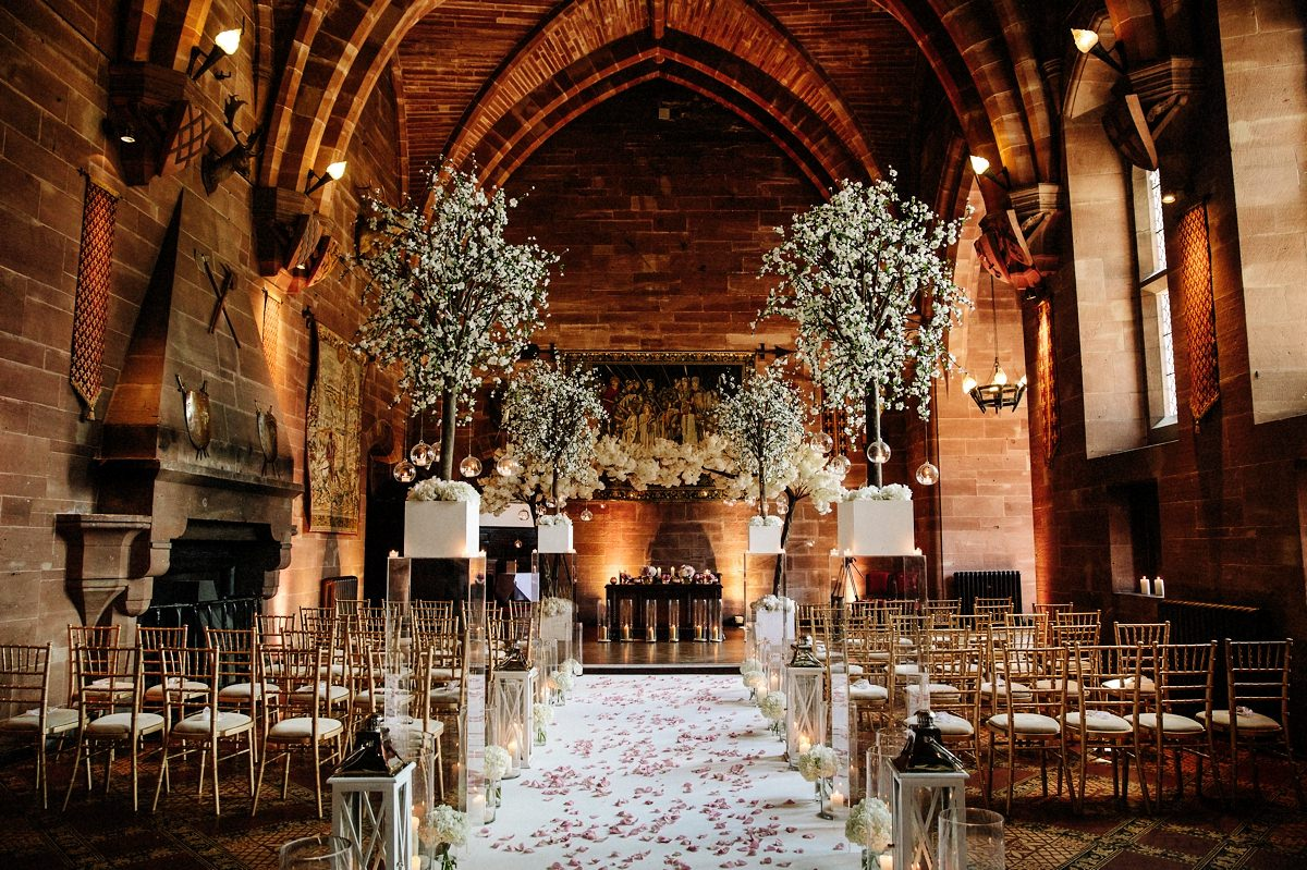 The Great Hall at Peckforton Castle dressed in floral displays and candles for the wedding ceremony