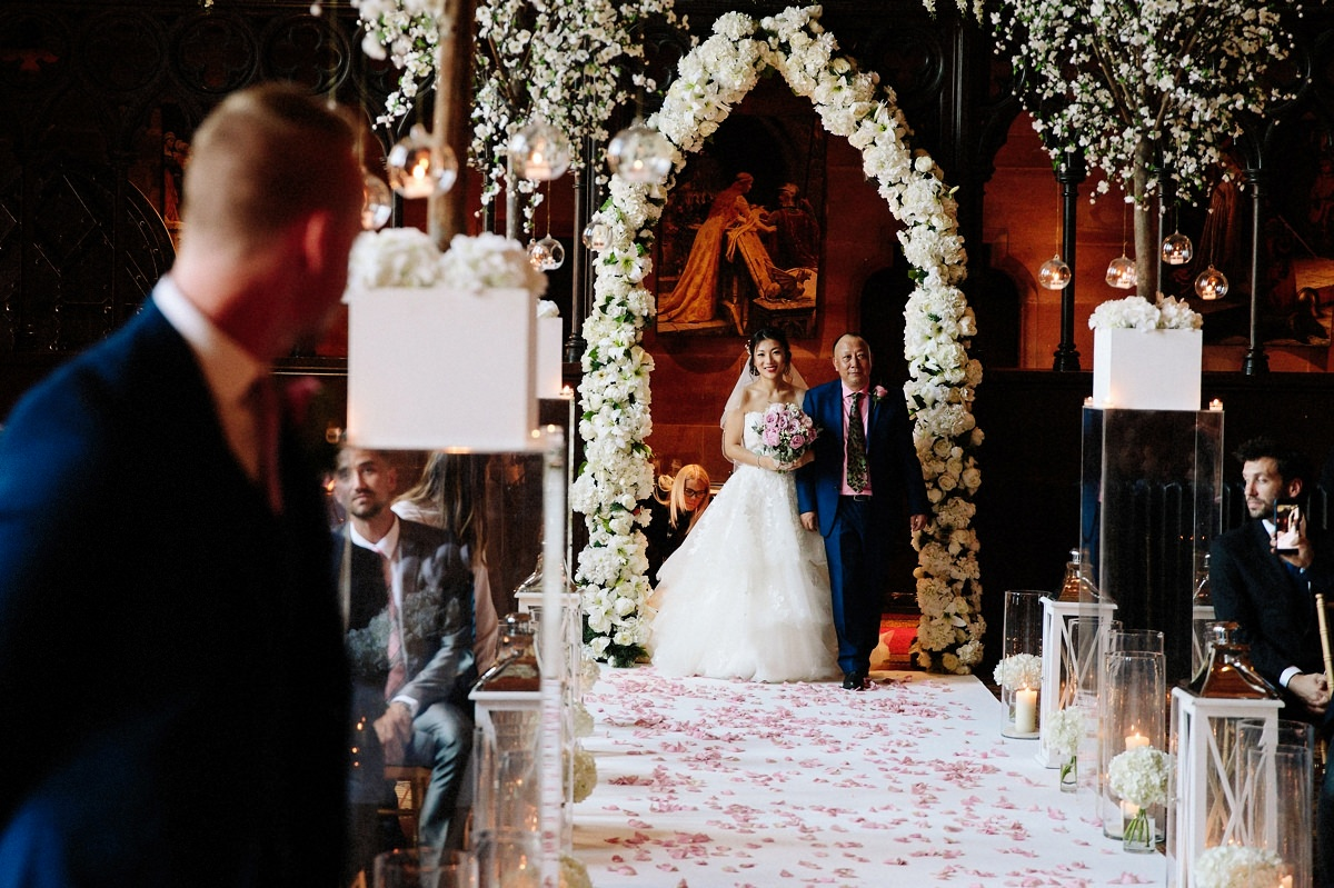 Bride walking down the aisle with her father with the groom looking on at Peckforton Castle