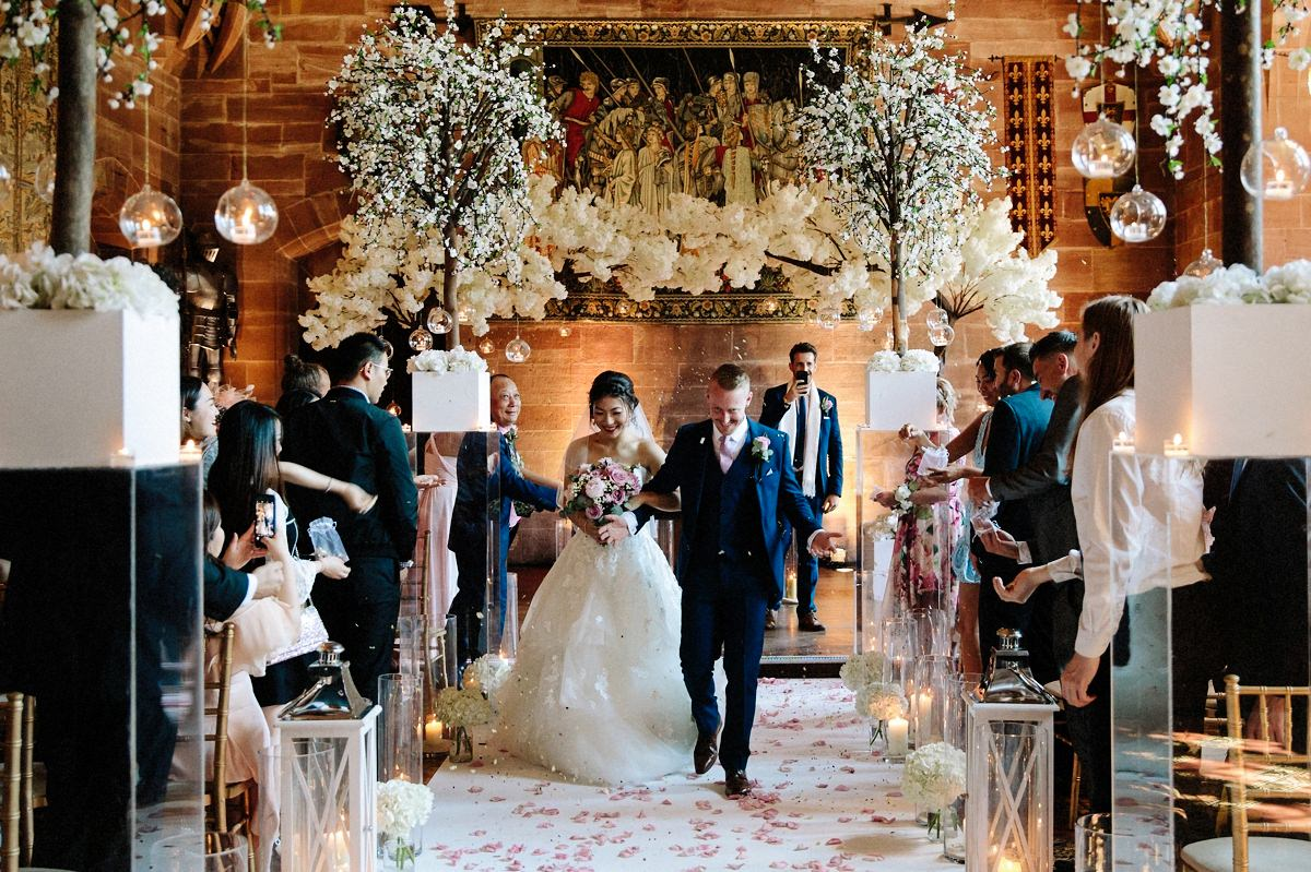 Bride and groom showered with confetti as they walk down the aisle at Peckforton Castle