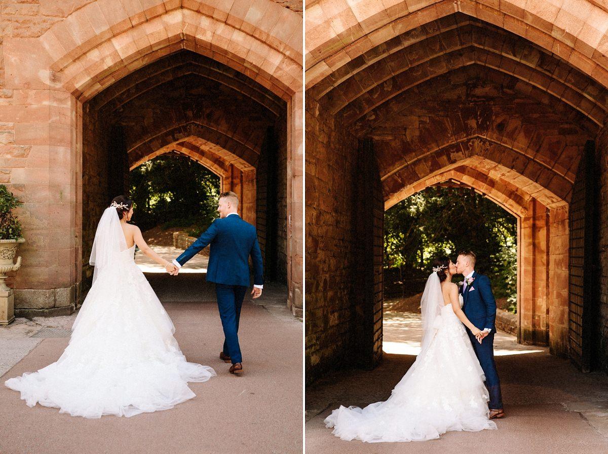 Bride and groom with the drawbridge at Peckforton castle