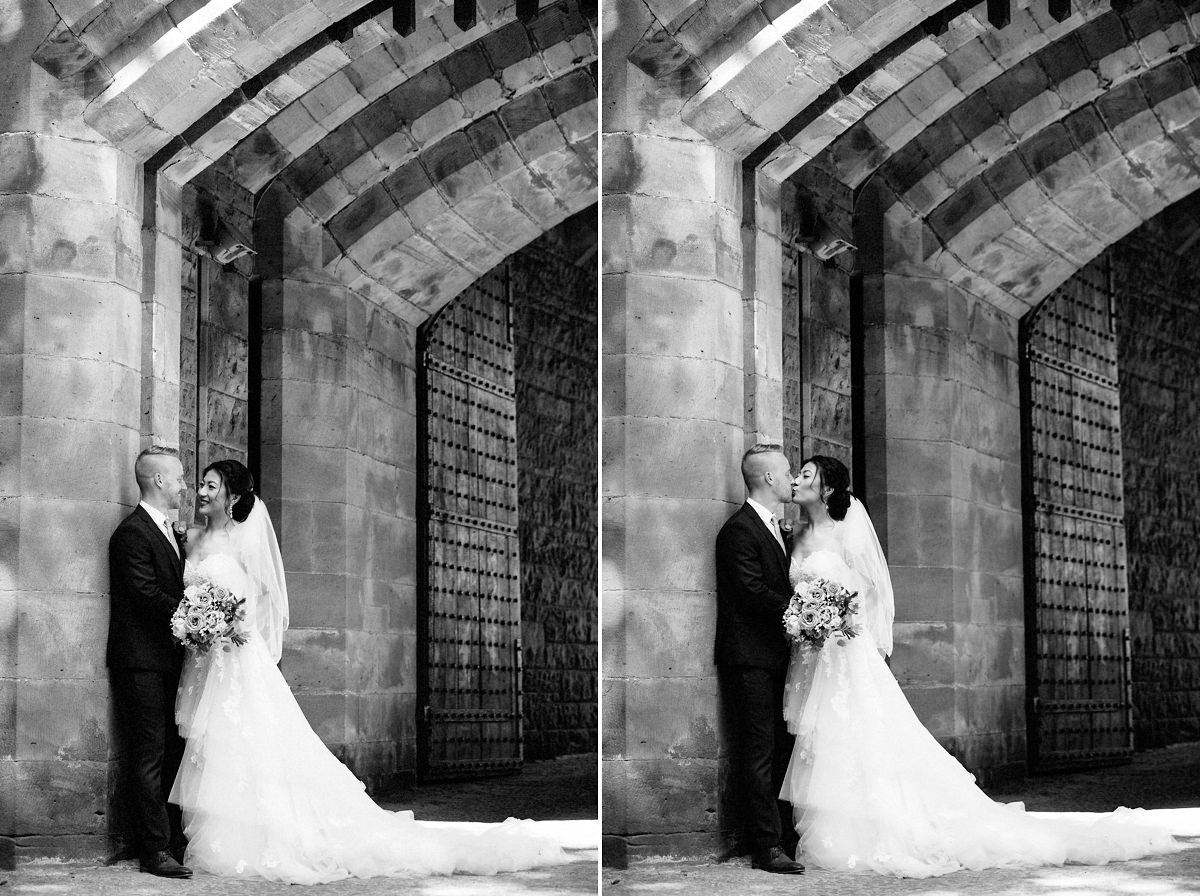 Black & white picture of the bride and groom with the castle walls at Peckforton