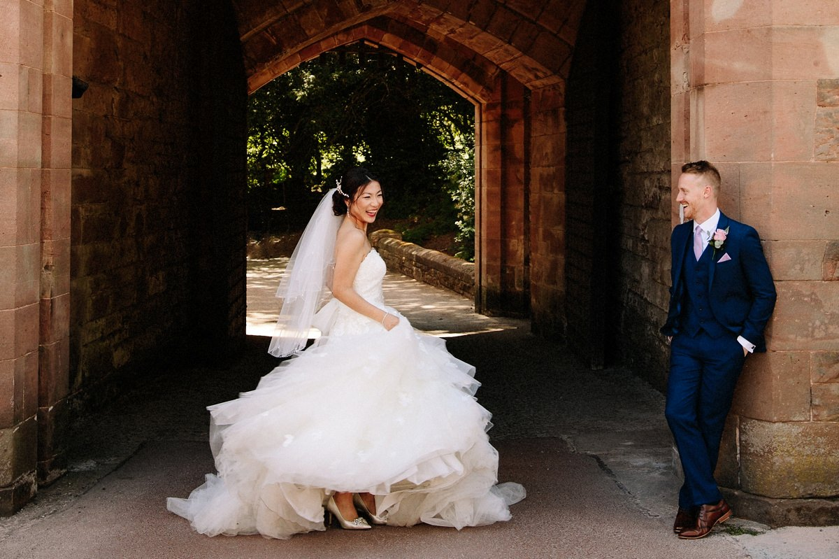 Bride swishing her wedding dress and having fun while her groom looks on