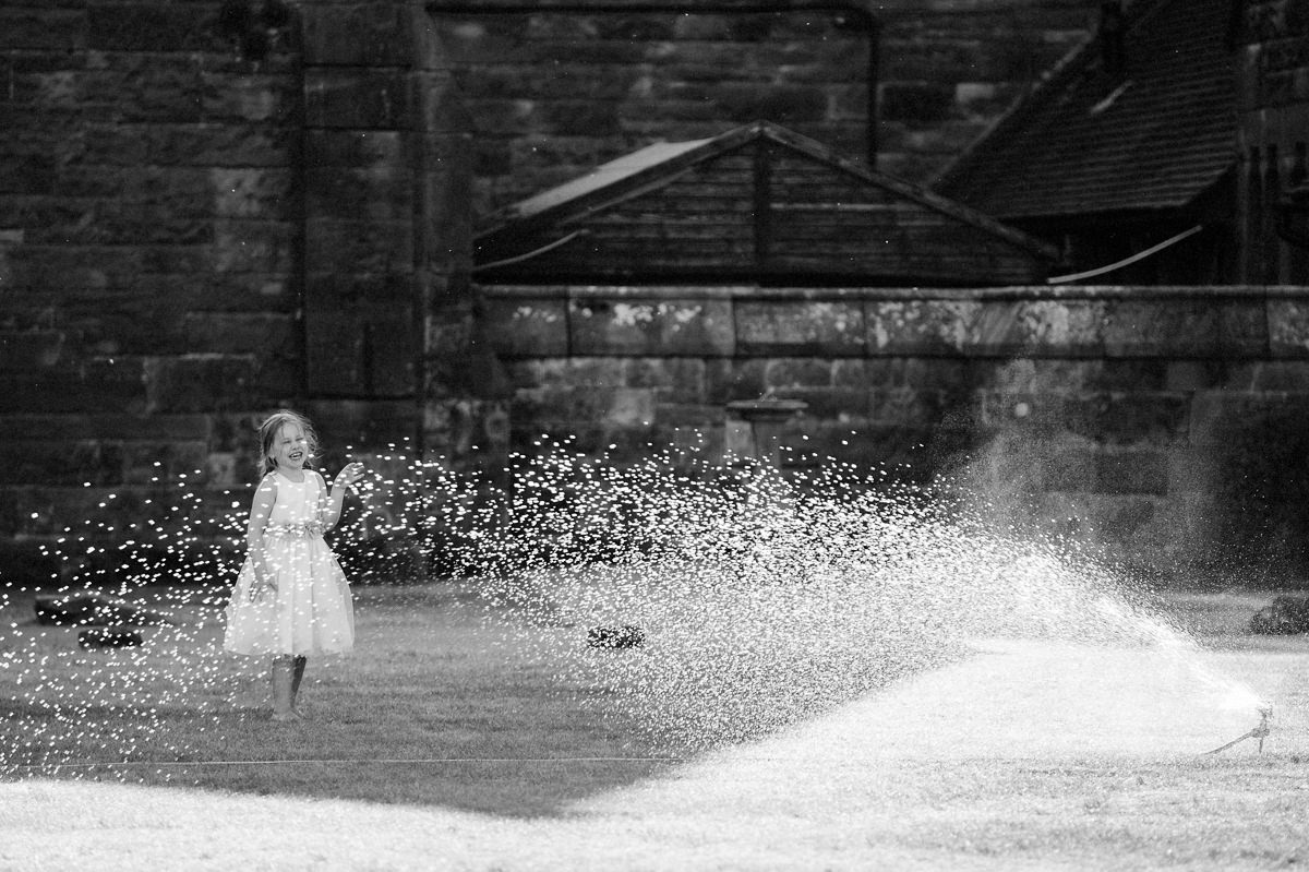 Flower girl playing and having fun with the water sprayer in black and white