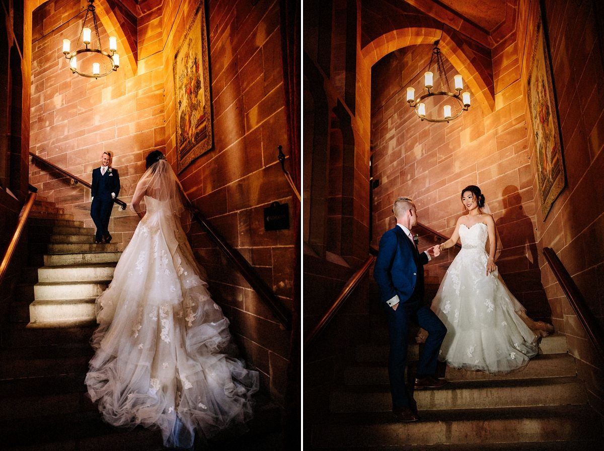 The gorgeous staircase at Peckforton Castle with the bride and groom