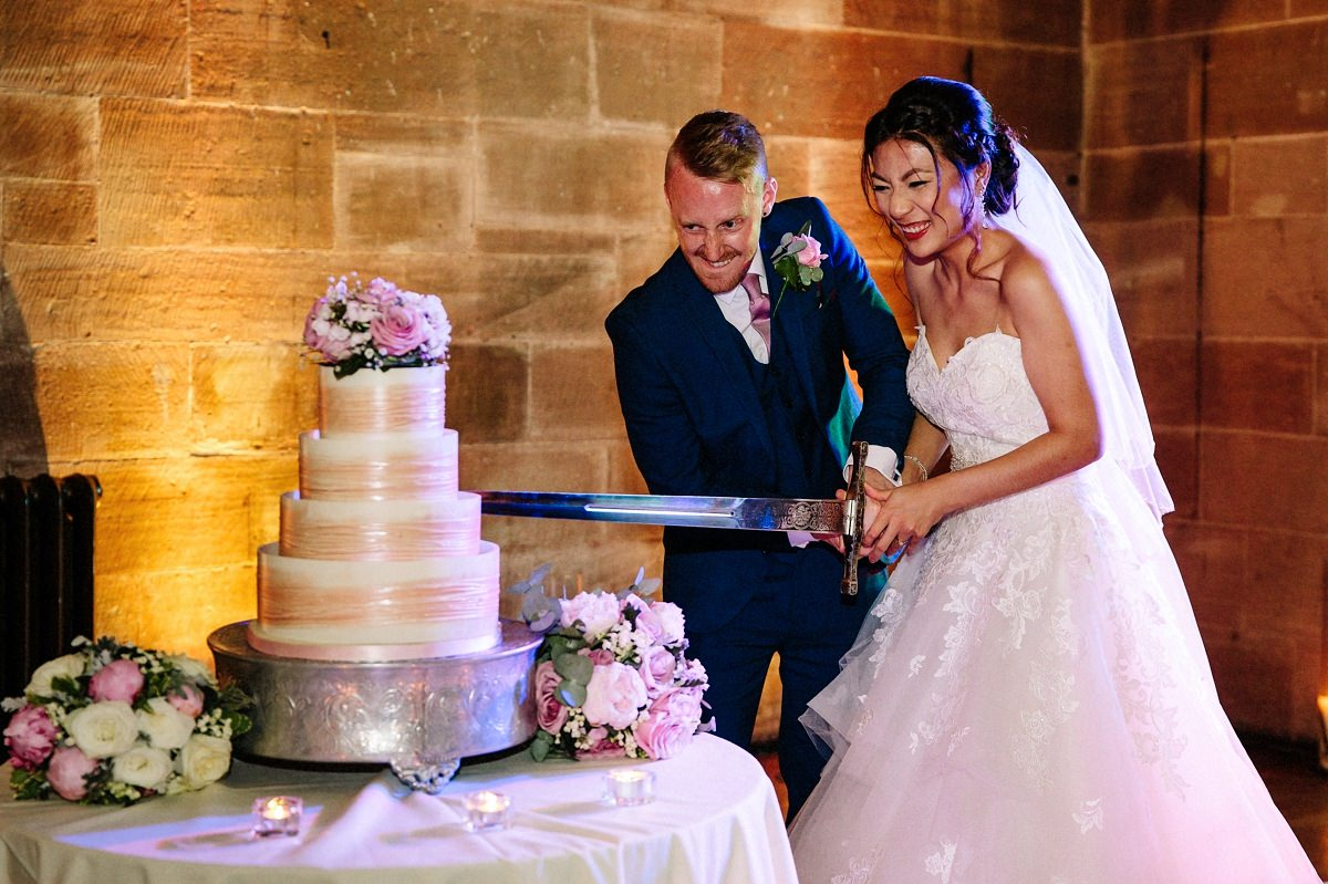 Bride and groom cutting the wedding cake with a sword at Peckforton Castle