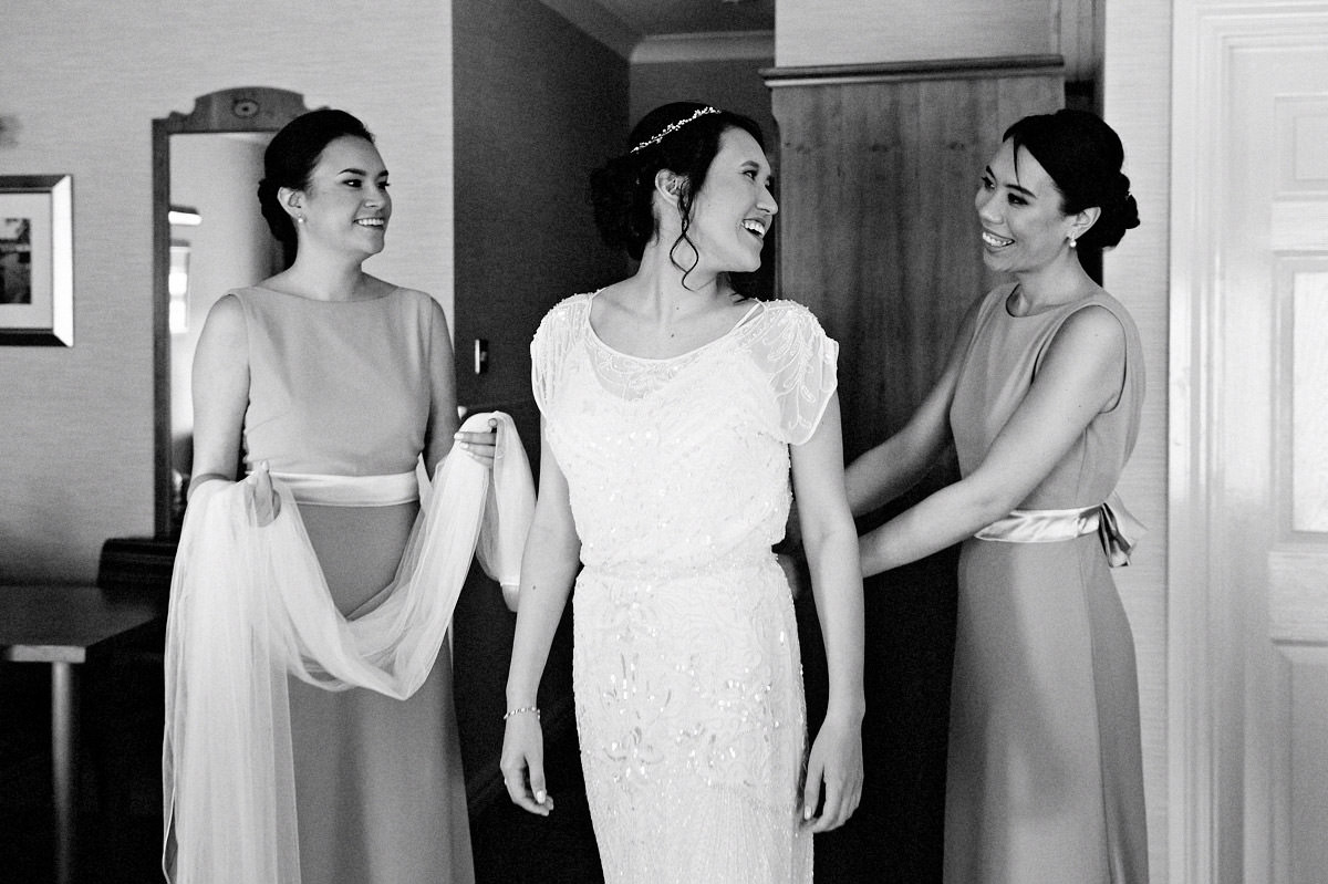 Bridesmaids helping the bride with her wedding dress before the wedding ceremony