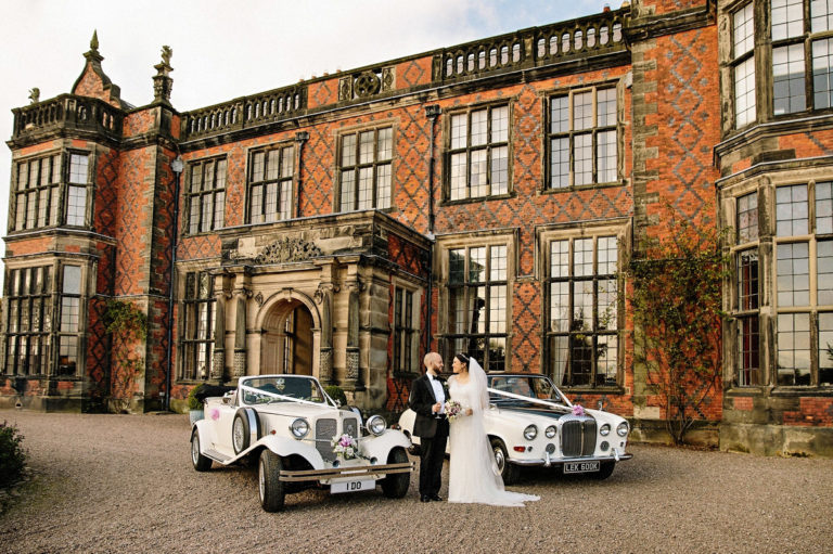 Bride and groom in front of the stately Arley Hall with two stunning wedding cars