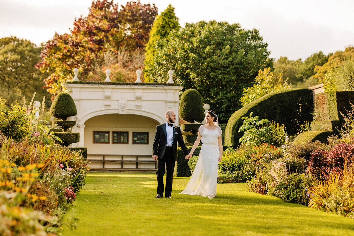 Bride walking with the groom in the gardens at Arley Hall