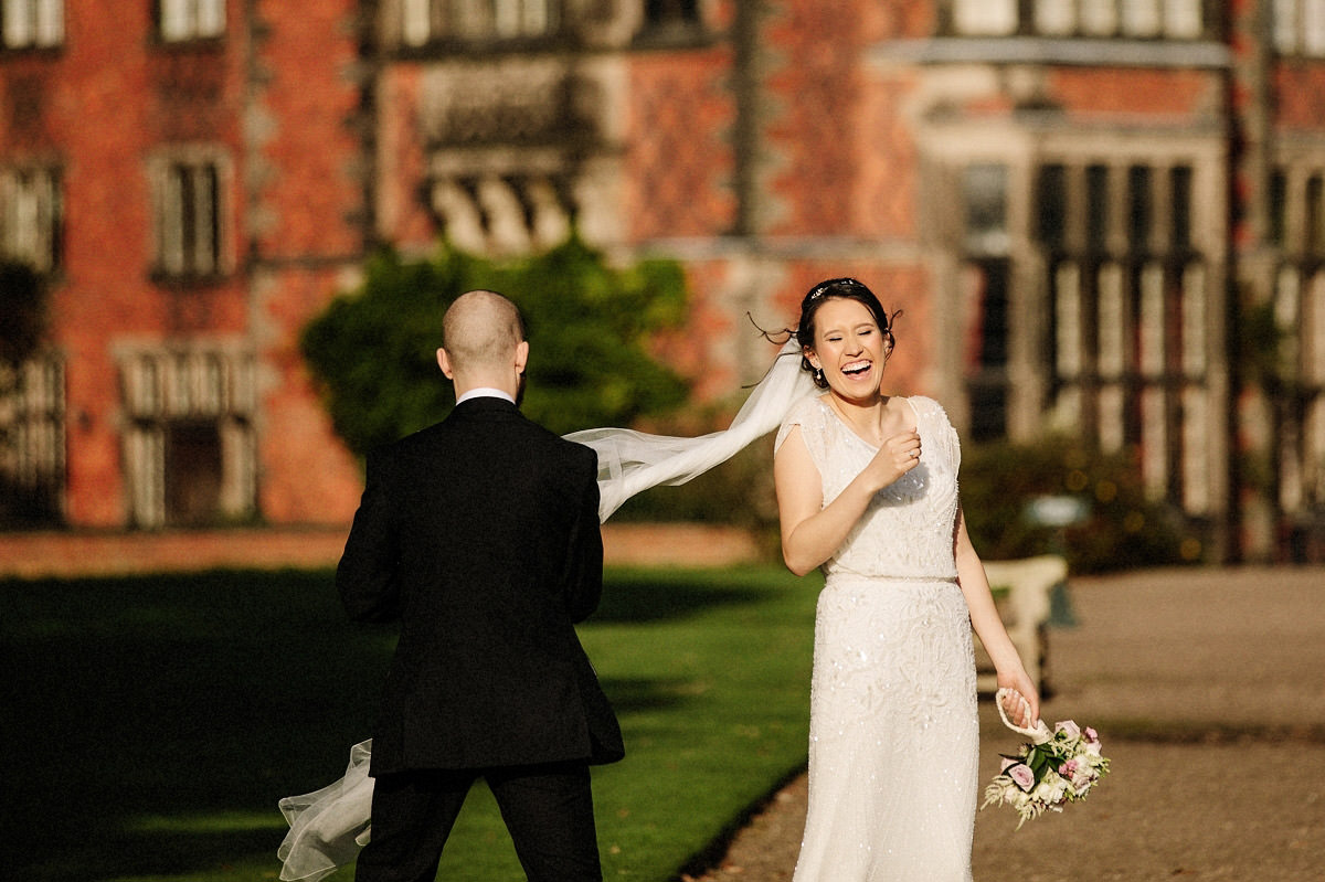 Fun natural moment with the brides veil blowing in the wind and the groom trying to catch it