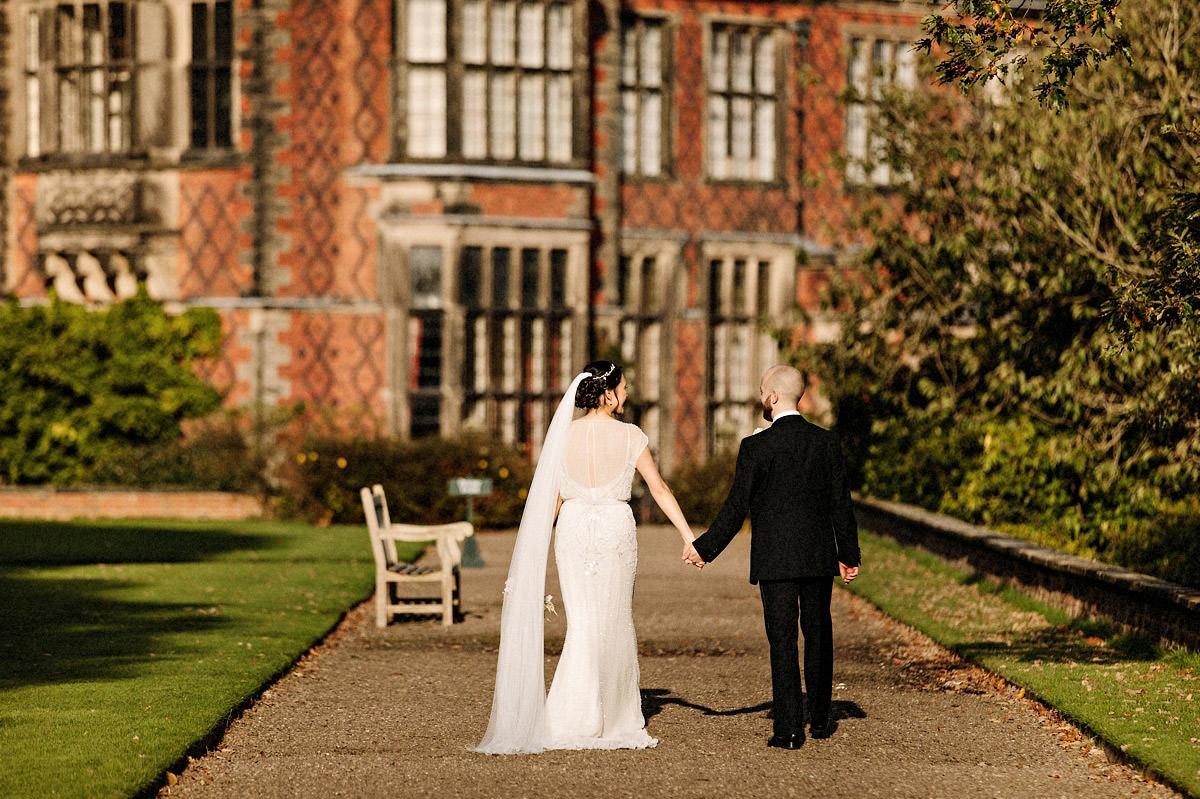 Bride and groom walking back towards Arley Hall for the wedding breakfast