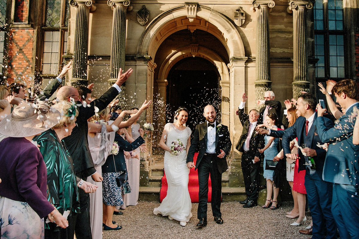 Fun confetti photo of the bride and groom and their wedding guests at Arley Hall